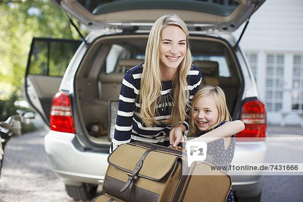 Mutter und Tochter tragen Gepäck zum Auto
