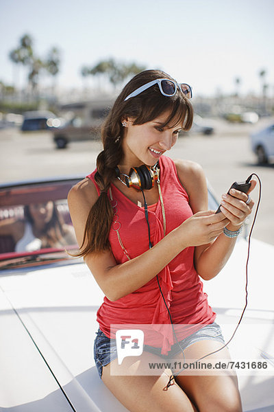 Smiling woman listening to mp3 player on car
