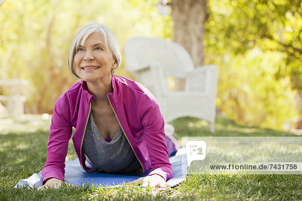 Older woman practicing yoga in backyard