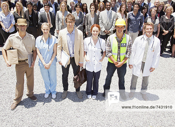 Porträt von lächelnden Profis und Arbeitern mit Geschäftsleuten im Hintergrund