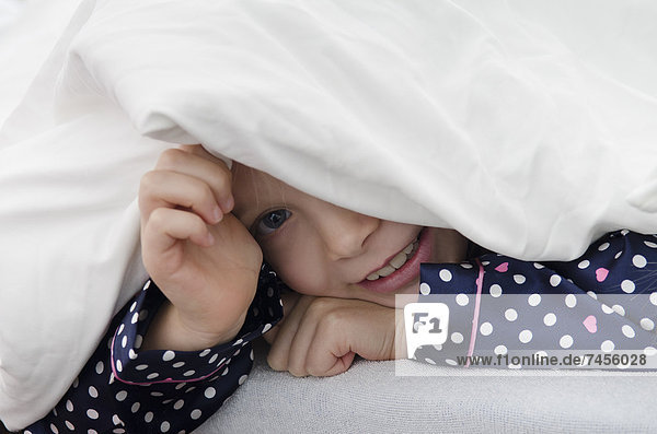Mädchen liegt unter der Bettdecke