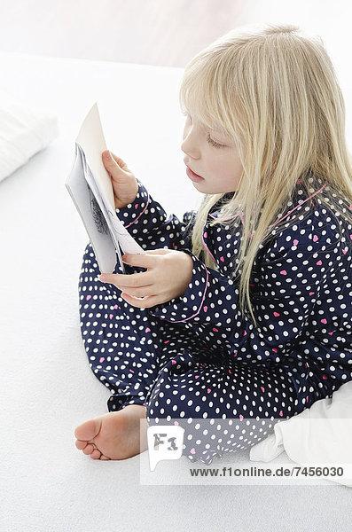 Mädchen liest im Bett