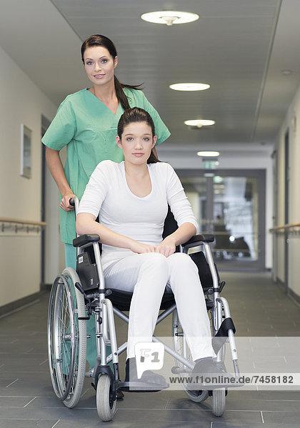 Krankenschwester bewegt Patientin im Rollstuhl