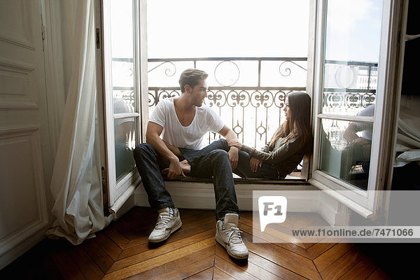 Paar auf der Fensterbank sitzend