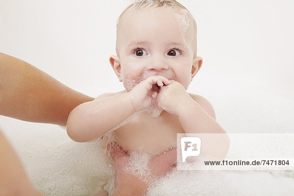Mutter wäscht Baby im Schaumbad