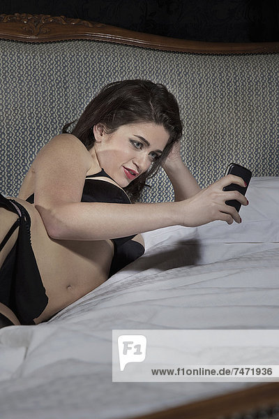 Frau beim Fotografieren in Unterwäsche