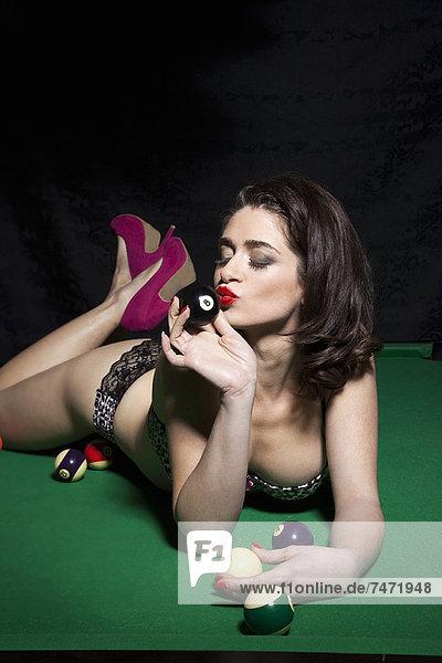 Frau in Dessous auf dem Billardtisch