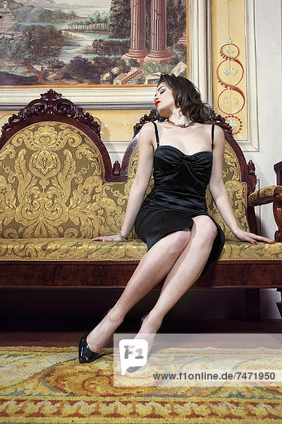 Frau in Dessous auf kunstvoller Couch