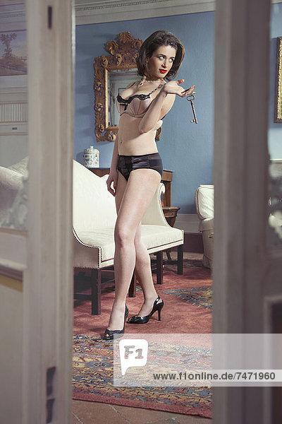 Frau in Dessous hält Schlüssel