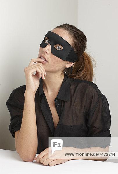 Frau mit Maske am Schreibtisch