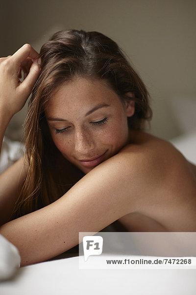 Lächelnde nackte Frau auf dem Bett liegend