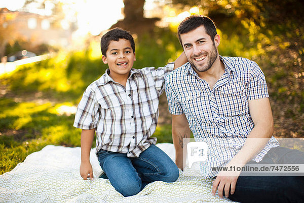 Father and son on picnic blanket
