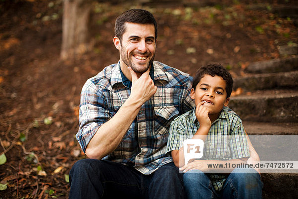 Father and son sitting on stone steps