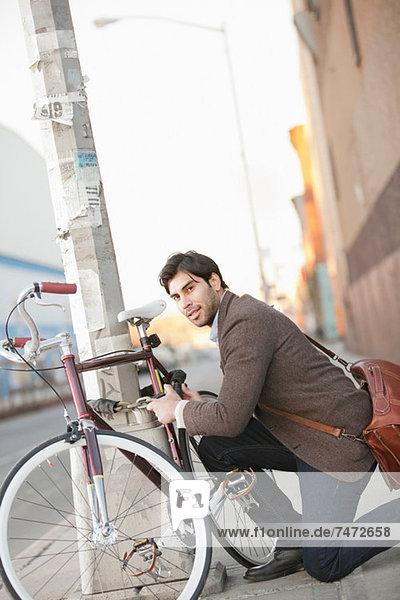 Mann sperrt Fahrrad auf der Stadtstraße