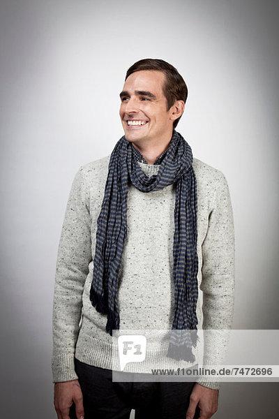 Lächelnder Mann mit Schal im Haus