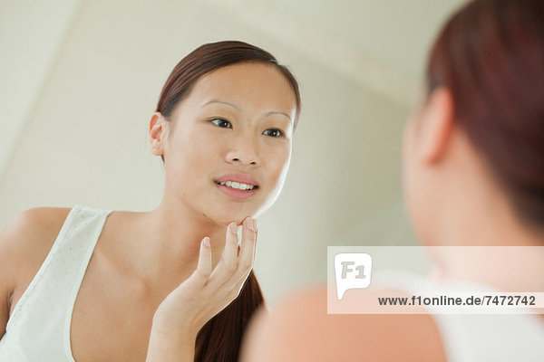 Woman examining her face in mirror