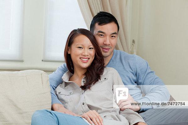 Lächelndes Paar entspannt auf dem Sofa