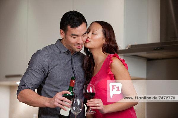 Paar mit Wein zusammen in der Küche