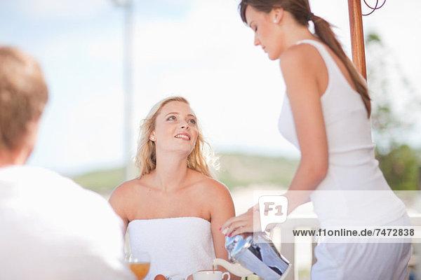 Kellnerin serviert Frau Kaffee am Tisch