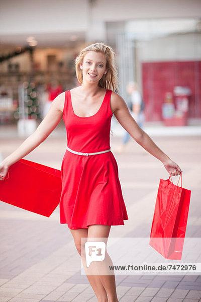 Frau trägt Einkaufstaschen im Einkaufszentrum