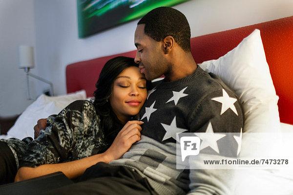 Lächelndes Paar entspannt auf dem Bett