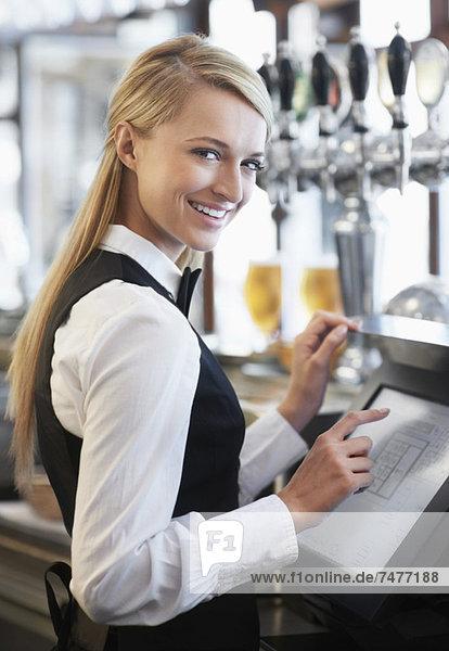 Young waitress using computer at restaurant counter
