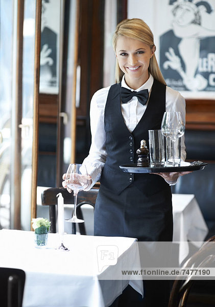 Portrait of young waitress holding tray and wine glasses