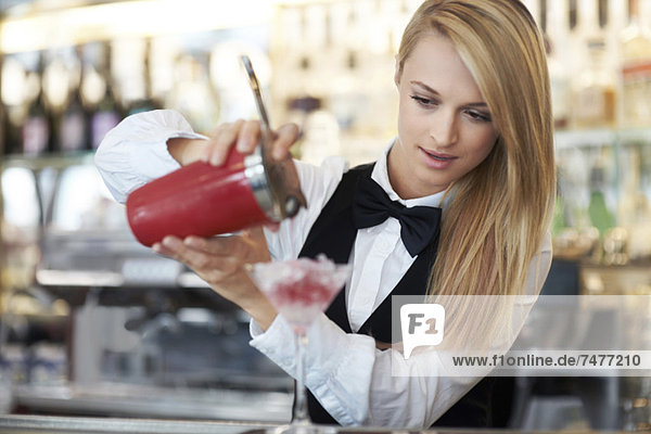 Young female bartender pouring cocktail