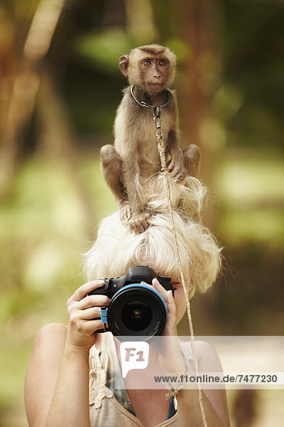 Portrait of female photographer with macaque monkey sitting atop her head