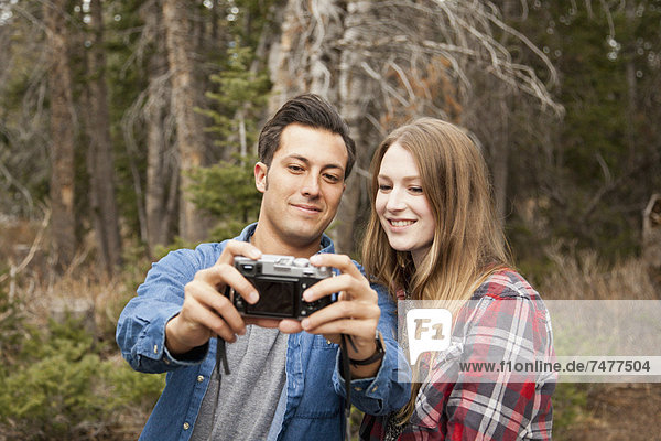 Young couple self photographing in non-urban scene
