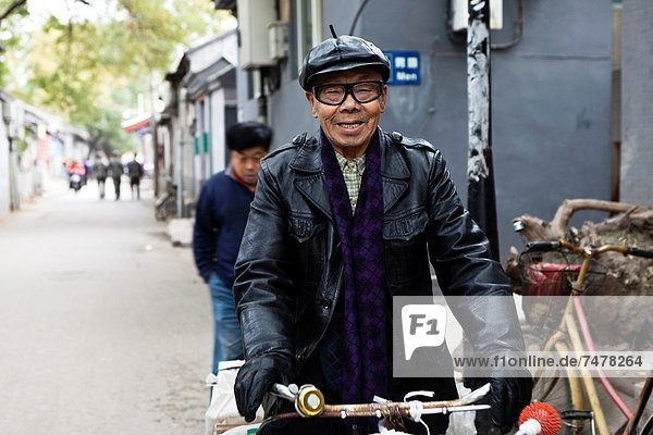 Chinese man on a bycicle in a hutong near Bell Tower  Beijing  China  Asia.