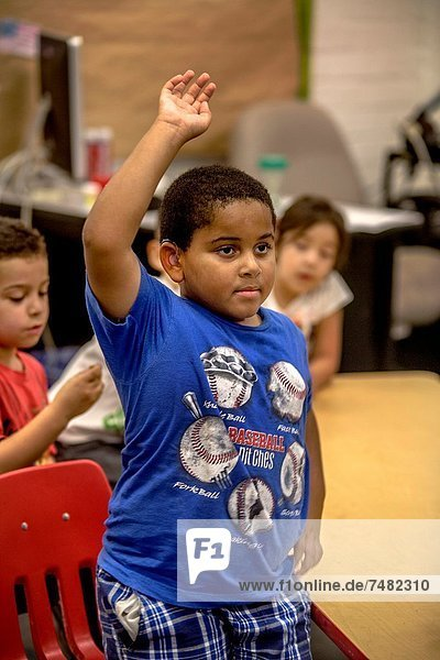 An enthusiastic hearing-impaired African American elementary school boy holds up his hand in class in Riverside  CA Note hearing aid in his ear
