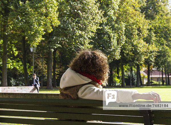 Young woman sitting on a bench watching a man speaking on the phone  Berlin  Germany  Europe
