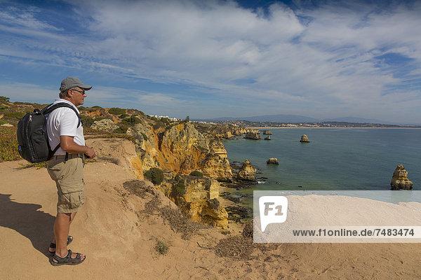56-jähriger Tourist genießt die Aussicht  Praia do Camilo  hinten Praia Dona Ana  Lagos  Algarve  Portugal  Europa