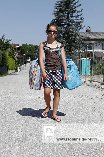Mädchen  11 Jahre  beim Tragen von großen Taschen  Ísterreich  Europa