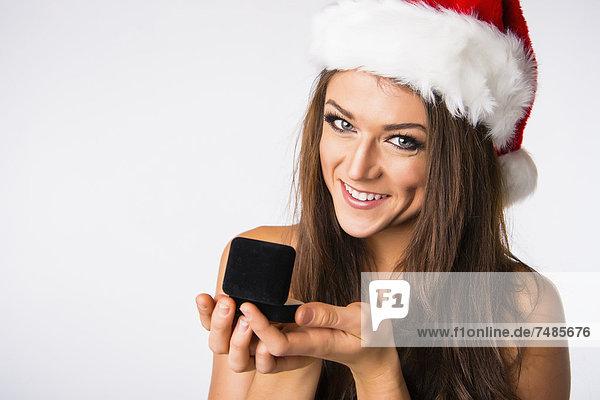 Junge Frau mit Weihnachtsmütze mit Schmuckkästchen  lächelnd  Portrait