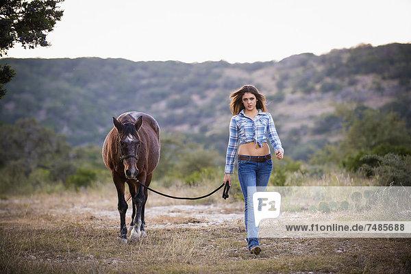 USA  Texas  Cowgirl beim Wandern mit Pferd