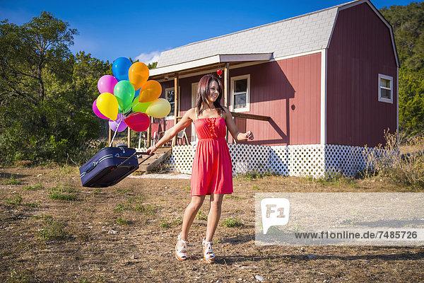 USA  Texas  Junge Frau mit Koffer und Ballon