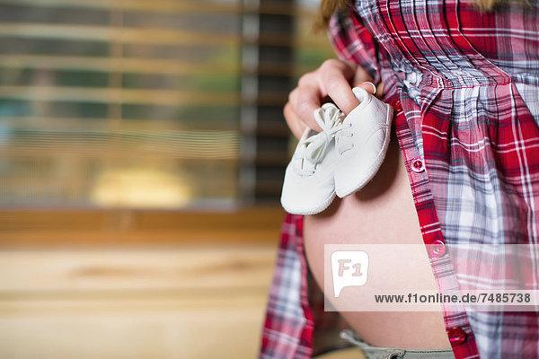 USA  Texas  Schwangere junge Frau hält Paar Babyschuhe am Bauch  Nahaufnahme