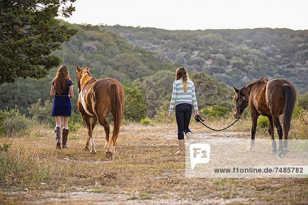 USA  Texas  Schwestern  die mit Quarterhorses am Berg spazieren gehen