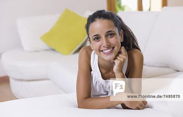 Teenagermädchen auf weißer Couch liegend  lächelnd  Portrait