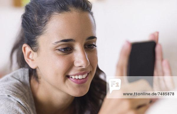 Teenager-Mädchen auf weißer Couch liegend und mit Smartphone  Nahaufnahme