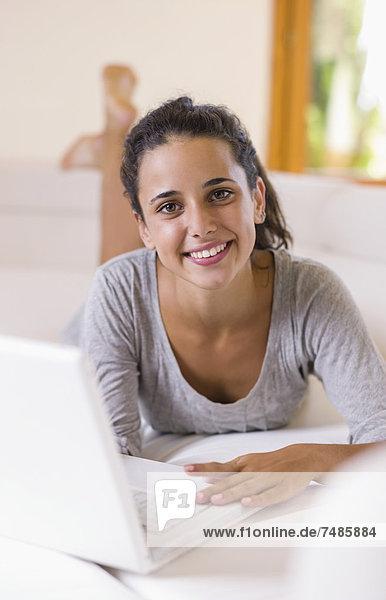 Teenagermädchen auf weißer Couch liegend mit Laptop  lächelnd  Portrait