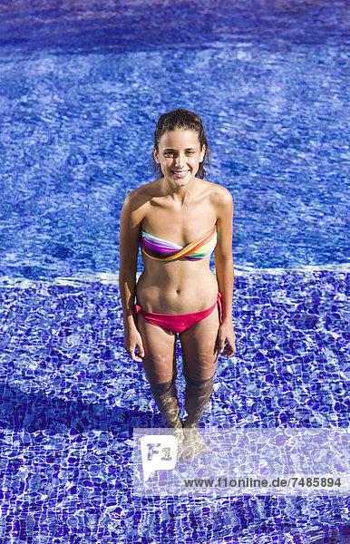 Spanien  Teenagerin im Schwimmbad stehend  lächelnd  Portrait