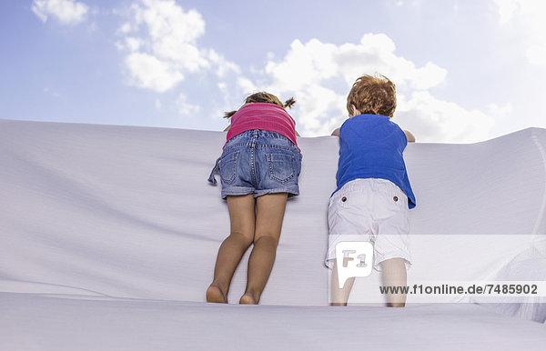 Spanien  Junge und Mädchen stehen und schauen über weiße Couch