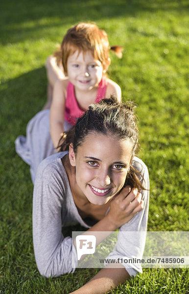 Spanien  Teenager Mädchen und Mädchen auf Gras liegend  lächelnd  Portrait