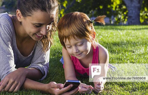 Spanien  Teenage Mädchen und Mädchen mit Smartphone auf Rasen  Nahaufnahme