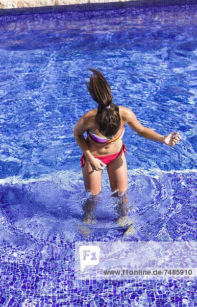Spanien  Teenager Mädchen spielt Luftgitarre im Schwimmbad
