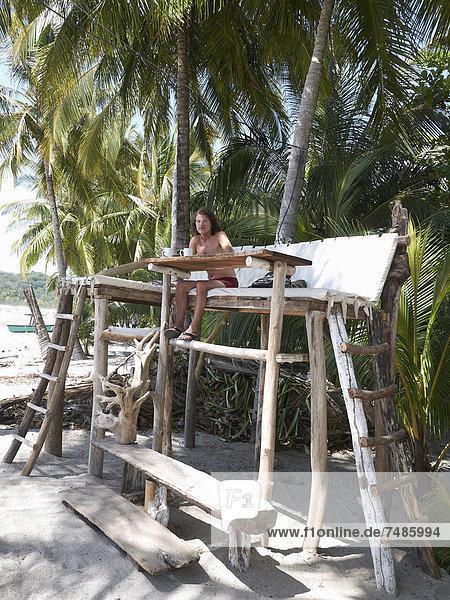 Mittelamerika  Costa Rica  Mann sitzend auf hölzernem Hochsitz unter Palmen