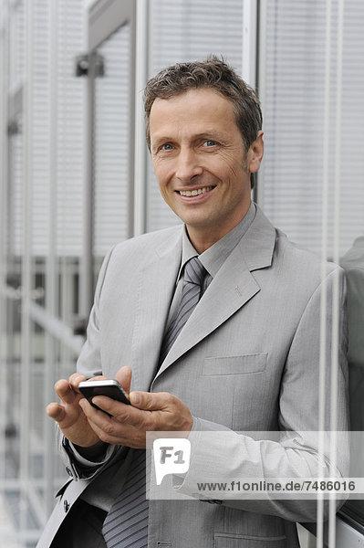 Europe  Germany  Bavaria  Businessman using mobile  smiling  portrait